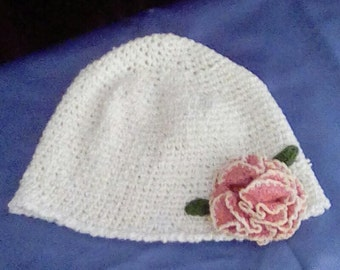 White crocheted winter hat with pink crocheted flower
