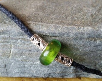 Necklace with tibetan silver & green lampwork bead on plaited black cord