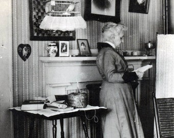 vintage snapshot photo 1915 Woman REads Book Birdcage Quilt Hangs on Wall Living Room Interior