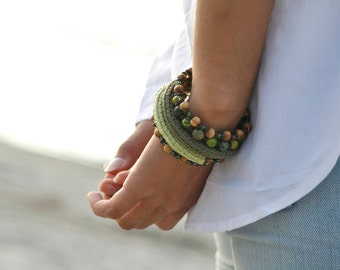 Crochet wrap bracelet with glass beads in different shades of olive green