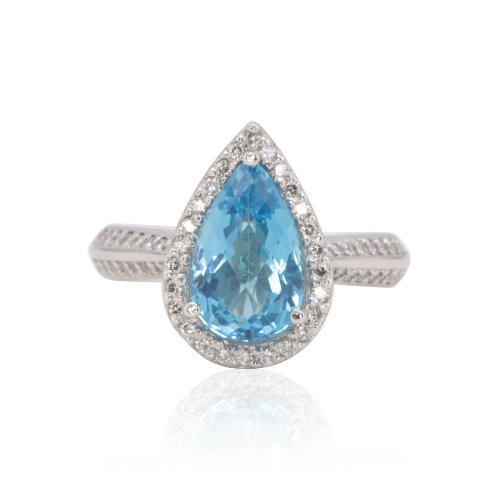 halo engagement ring with 2 carat pear cut blue topaz and