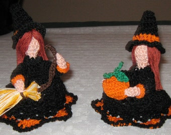 Two Little Witches, dressed for Halloween, one with a broom, the other with a pumpkin