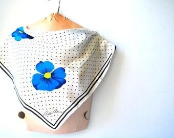 Boho vintage 70s white , silky polyester scarf with a tiny black polka dot  and royal blue  single flowers. Made by Bill Blass.