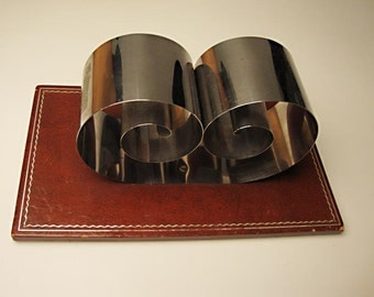 Retro Book Holder:  Chromed spring steel, faux leather - holder expands to securely hold as many as 6 books., fine vintage condition