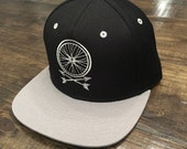 Wheel and Arrows Snapback Hat