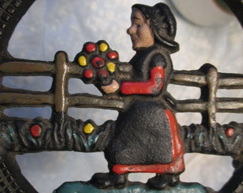 Vintage Trivet 1960s Black Cast Iron AMISH GIRL Holding Wiht FLowers Painted country