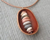 Beach pebbles held by seed pod -  natural pod jewelry handmade in Australia - sacred earth jewellery