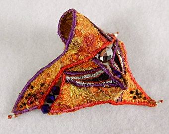 Textile brooch in orange and purple