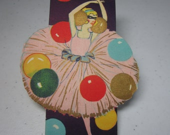 Art deco unused die cut 1920's-30's gold gilded bridge tally shows a masked ballerina in pink dress tutu dancing with colorful balloons