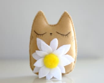 Cute cat doll with a camomile flower