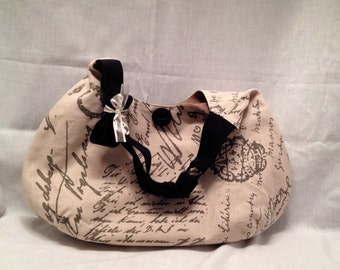 Adult purse: Soft grey-brown writing on cream over-the-shoulder hobo purse with magnet closure and inside pocket.