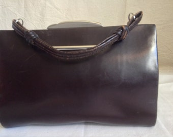 Brown leather pouch, clasp metal, anse à nodes, lay hands.