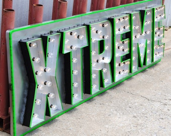 Metal multi-letter lighted hanging marquee sign with metal backing box and bulbs.