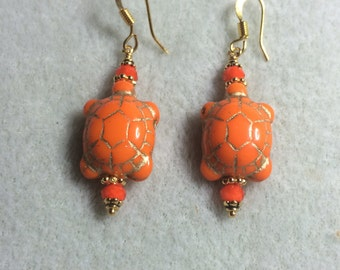 Opaque orange Czech glass turtle bead earrings adorned with orange crystal beads.