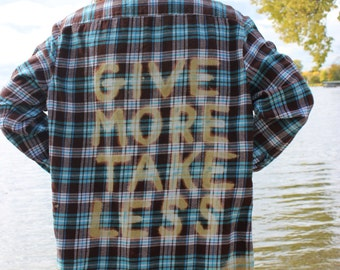 Give More Take Less bleached onto back of turquoise and brown plaid flannel shirt
