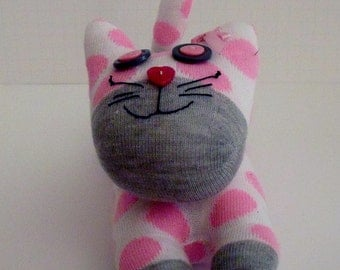 Sock Cat Made with a White Sock With Pink Dots and Gray Accents and Adorned with Button Eyes and Nose and Hand Stitched Face and Bow on Ear