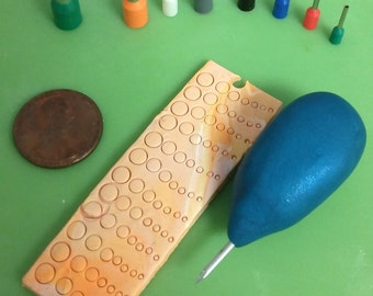 Polymer clay circle cutters with texture  needle tool.