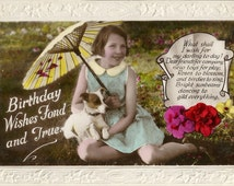 Birthday wishes, c1920s, girl with puppy, paper parasol, flower garden, Art Deco greetings, tinted photo, embossed border  (rppc/gr3)