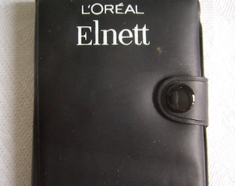"Pocket Calendar and directory, black plastic, advertising ""L ' Oréal elnett Hairspray"""