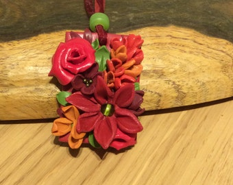 Polymer clay-floral design in burgundy, red, orange and green on a burgundy base