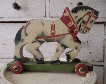 Old vintage wooden horse drawing horse on wheels shabby wooden toys