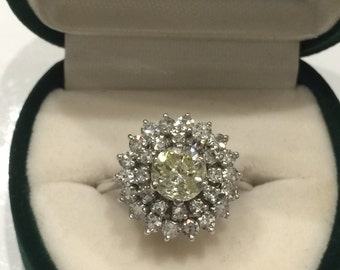 Diamond Cluster Ring in 18K White Gold. Central stone is a Fancy Yellow Diamond of 0.85ct. Vintage circa 1954.