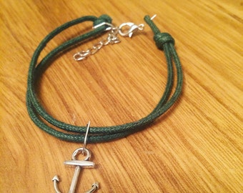 Green string bracelet with clasp and anchor.