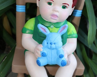 Baby boy doll on rocking chair