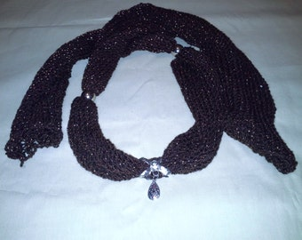 Sweater scarf with silver bow accent and rust flower pendant with silver accessories.