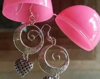 Silver earrings with dangle heart on bottom.