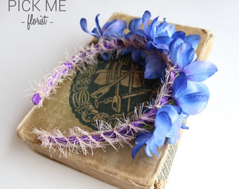 Headband of artificial blue flowers finished with pink ribbon. Ideal festival wear of fake delphinium flowers with pink and purple finish.