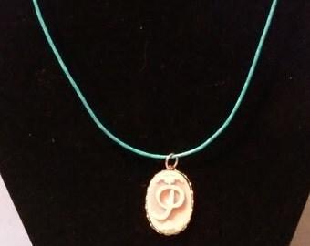 "pink ""P"" pendant on a blue hemp necklace"