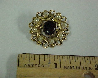 Small black brooch with pearl like stones