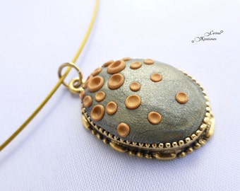 Necklace with a pendant made from polymer clay with flat points gold and bronze