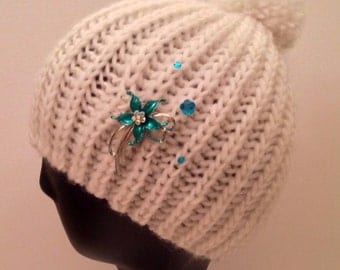White knit beanie embellished/decorated with turquoise pin