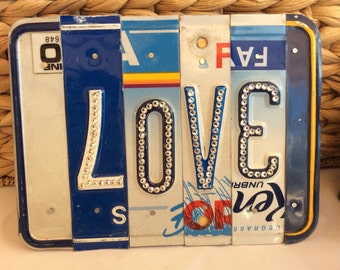 Custom recycled plates forming the word with Swarovski crystals!