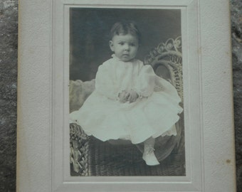 Precious vintage parlor photo of small child on rattan chair