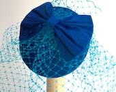 Peacock blue bow fascinator,  birdcage veil.