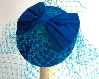 Peacock blue bow fascinator,  birdcage veil.