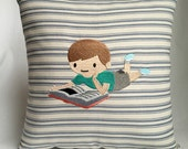 """Young boy reading 12""""x12"""" pillow, embroidered on striped fabric"""