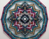 Breaking Free, an all wool, 12-sided, 24 inch Ojo de Dios, handcrafted by Sami Herbert
