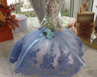 Large half doll, about 5 inches, with blue dress and flowers. about 10 inches high in all