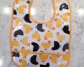 Chicken-patterned bib, colorful orange, yellow and black, cotton laminate