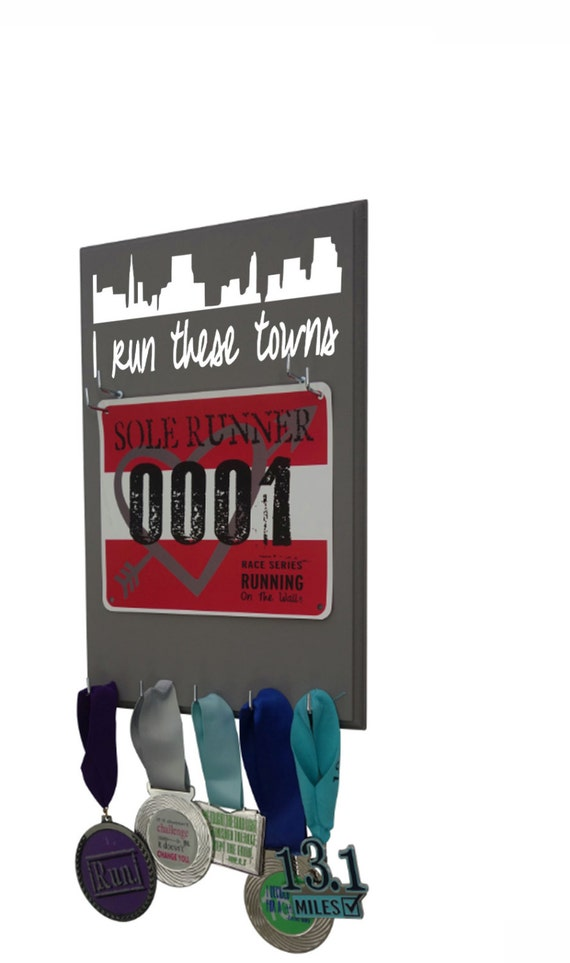 Display your race bibs and running medals with this I run these towns or I run this town holder