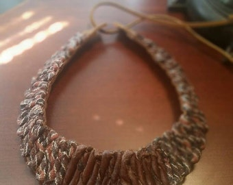 Leather collar necklace with leather and fabric detail.