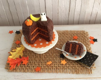 Miniature Halloween Cake With a Pumpkin, a Moon, and a Ghost and a Slice Of Cake
