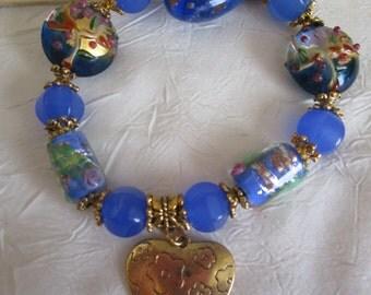 "Bracelet doré en perles lampwork bleues ""Coeur""."
