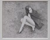amy, graphite drawing on paper in black and silver frame, very detailed miniature drawing of a woman in a black coat sitting on grass, art