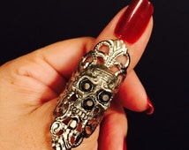 Skull ring made in dull silver color filigree metal, adorned with a small skull on top with crystal eyes.