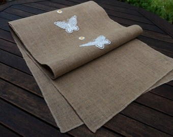 Table runner made from burlap/hessian with butterfly and flower lace. Looks and feels vintage.